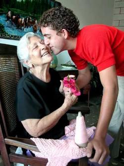 anciana recibiendo flores de su nieto