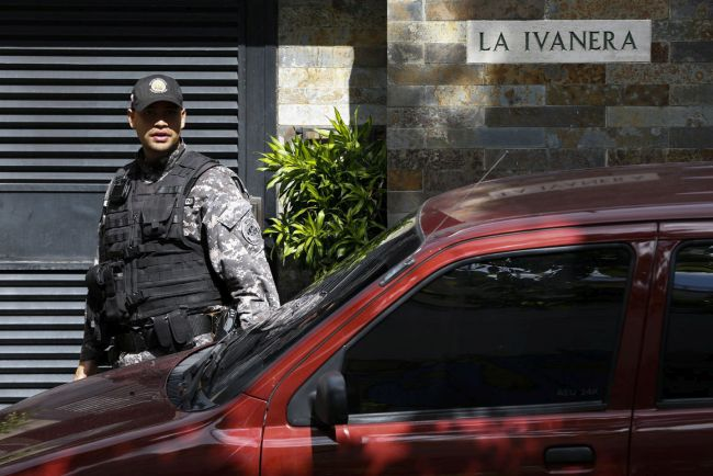 A police officer stands guard outside the house of former Caracas police commissioner Ivan Simonovis in Caracas